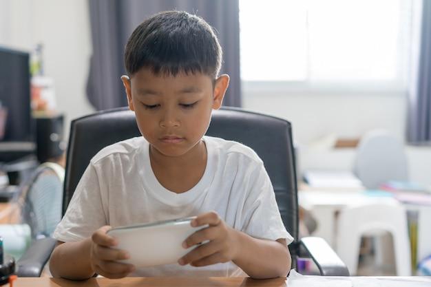 Rapaz asiático usar t-shirt branca está jogando smartphone atentamente