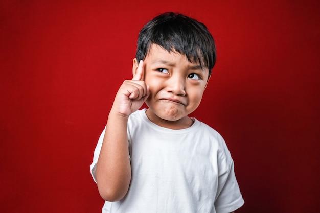 Rapaz asiático vestindo camiseta branca sobre fundo vermelho, apontando o dedo para cima com a ideia bem sucedida. saído e feliz. número um.