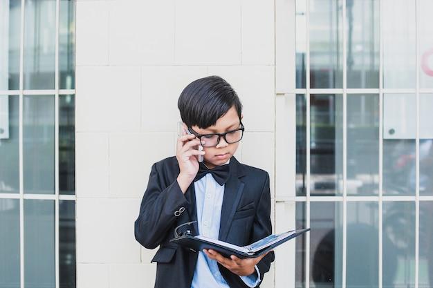 Rapaz asiático vestindo terno preto vintage e óculos fazendo uma ligação por telefone enquanto olha um caderno