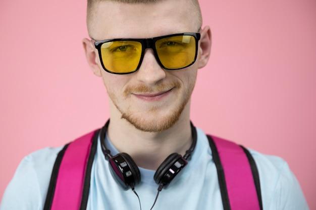 Rapaz astuto com olhos estreitos em óculos e fones de ouvido no pescoço sorri suavemente