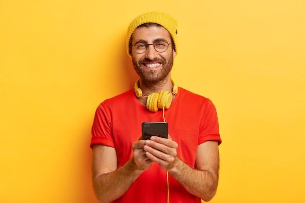 Rapaz atraente e alegre com cerdas, usa chapéu brilhante e camiseta vermelha