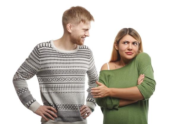 Rapaz barbudo bonito vestido de suéter sorrindo e olhando para uma mulher atraente que fica de pé em postura fechada com os braços cruzados, sentindo-se confusa por não gostar ou entender sua piada boba