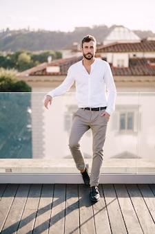 Rapaz barbudo estiloso de camisa branca e calças leves em um terraço na cobertura em florença, itália