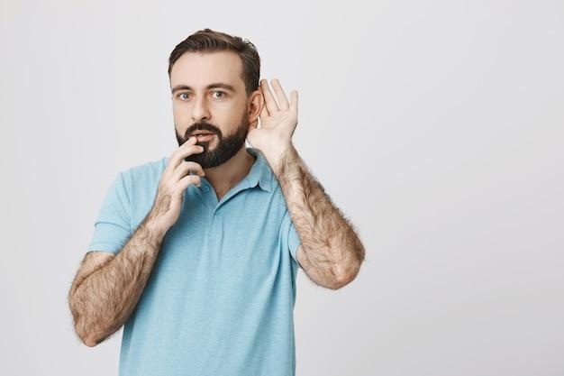 Rapaz barbudo intrigado bisbilhotando, tentando ouvir uma conversa