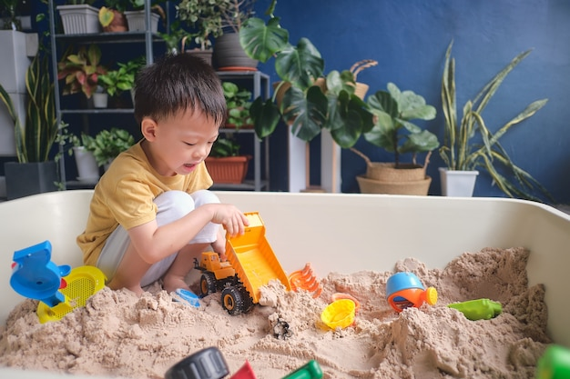 Rapaz bonito asiático brincando com areia sozinho em casa, criança brincando com brinquedos de areia e maquinários de construção em jardim urbano