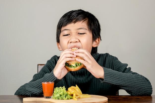 Rapaz bonito asiático comendo um hambúrguer delicioso de felicidade