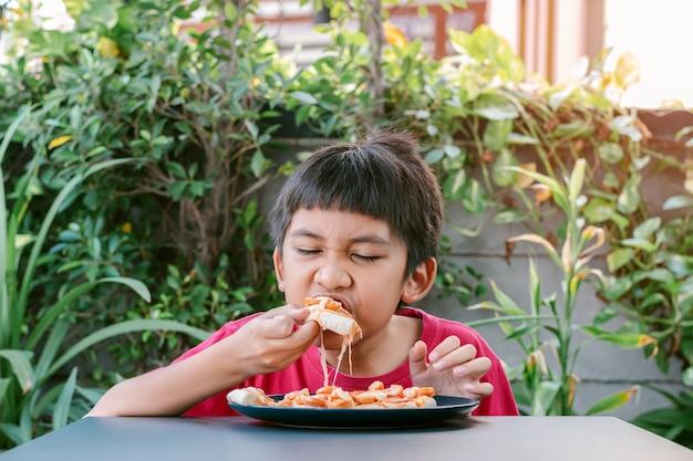 Rapaz bonito asiático de camisa vermelha comendo pizza deliciosamente e feliz.