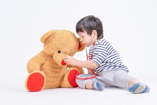 Rapaz bonito asiático jogando um estetoscópio de uso médico, verificando o grande urso de pelúcia sentado no chão