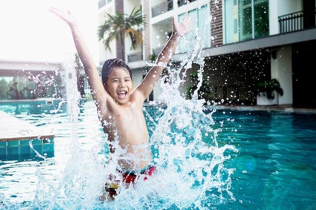Rapaz bonito asiático pulando fazer respingos de água na piscina