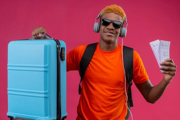Rapaz bonito com mochila e fones de ouvido segurando uma mala de viagem