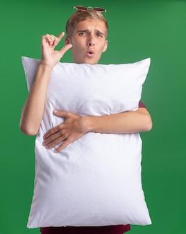 Rapaz bonito desagradável vestindo uma camisa vermelha abraçou o travesseiro mostrando o tamanho isolado na parede verde