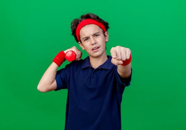 Rapaz bonito desportivo confiante com fita para a cabeça e pulseiras com aparelho dentário segurando halteres, olhando e apontando para a frente, isolado na parede verde com espaço de cópia