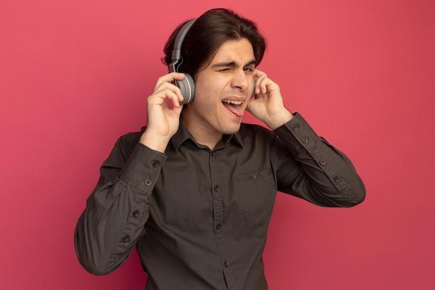 Rapaz bonito e piscando vestindo uma camiseta preta com fones de ouvido mostrando a língua isolada na parede rosa