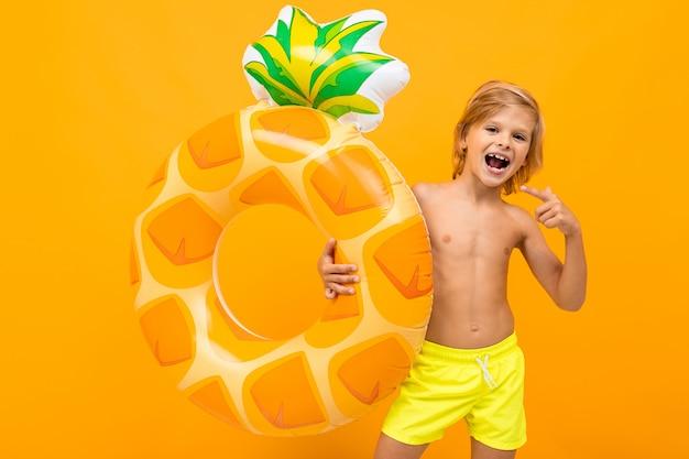 Rapaz bonito em calção de banho detém um anel de borracha, sorrisos e gesticula isolado na laranja