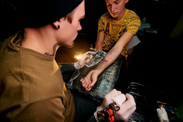 Rapaz bonito em um chapéu preto e com tatuagens, bate uma tatuagem no braço, salão de tatuagem