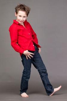 Rapaz bonito em uma camisa vermelha e calça jeans em uma parede cinza. uma criança no negócio de modelagem está posando.