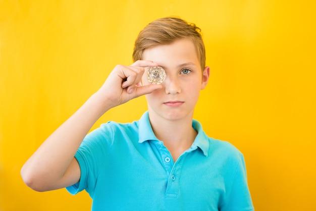 Rapaz bonito olha através de um prisma de vidro. conceito médico, de visão e implantação