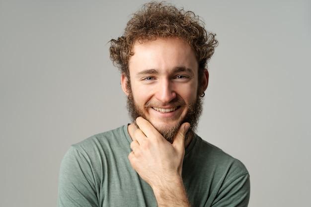 Rapaz bonito posando no estúdio com uma camiseta verde oliva, olhando para a frente, tocando seu queixo isolado na parede branca