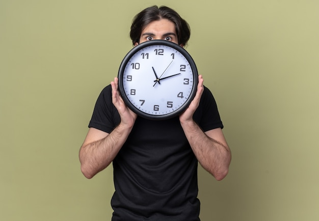 Rapaz bonito preocupado, vestindo uma camiseta preta, rosto coberto com um relógio de parede isolado na parede verde oliva