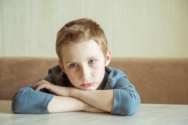 Rapaz bonito sentado com as mãos postas no pensamento