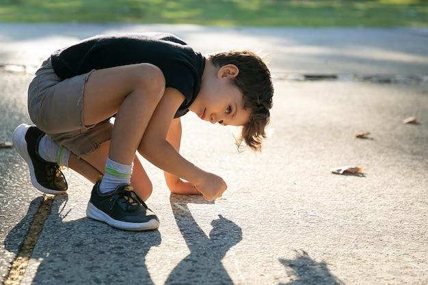 Rapaz bonito sério desenho na superfície do parque infantil com pedaços coloridos de giz. vista lateral. conceito de infância e criatividade