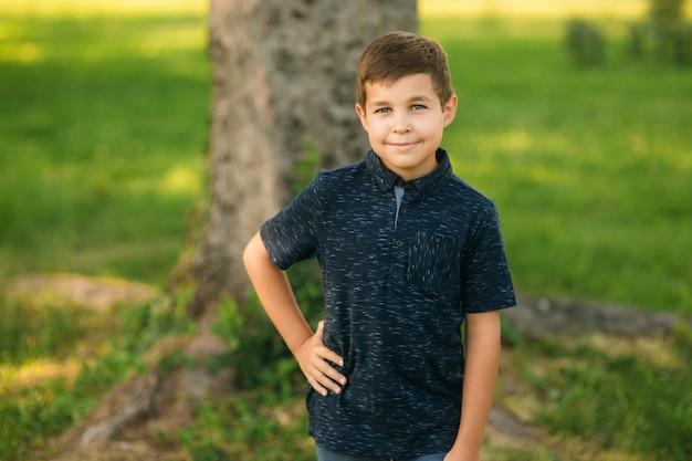 Rapaz bonito, sorrindo e posando para o fotógrafo. criança alegre caminha pelo parque. tempo ensolarado