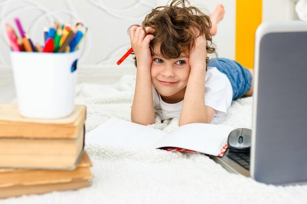 Rapaz cacheado está envolvido no computador. estudante agarra sua cabeça e olha para o monitor. conceito de dificuldades de ensino em casa, estudo à distância.