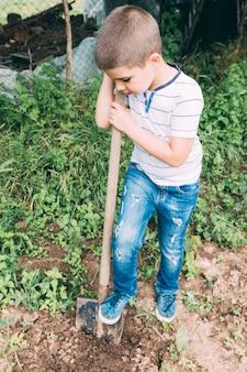Rapaz, cavando o solo no jardim