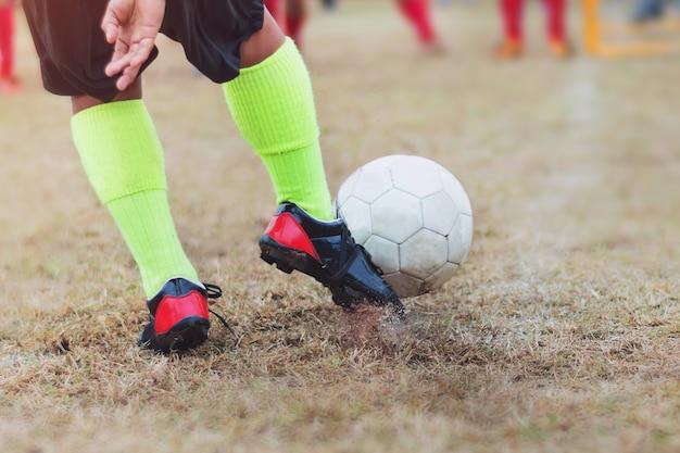 Rapaz chute futebol futebol no campo de esporte