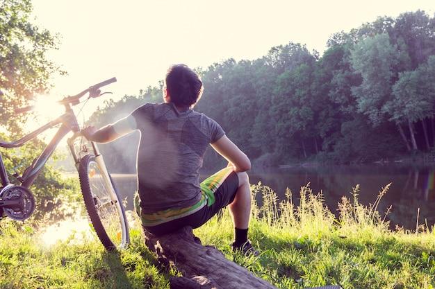 Rapaz ciclista senta-se e parece longe perto do rio