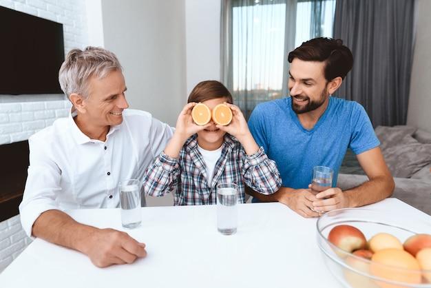 Rapaz cobre os olhos com frutas enquanto está sentado na mesa.