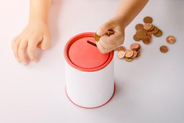 Rapaz colocando dinheiro em um banco de moedas