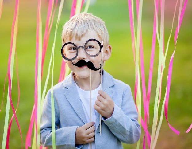Rapaz com bigode de papel engraçado e óculos