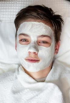 Rapaz com máscara facial em salão de beleza