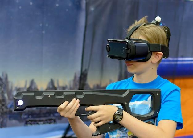Rapaz com óculos de realidade virtual com arma a jogar no jogo de tiro