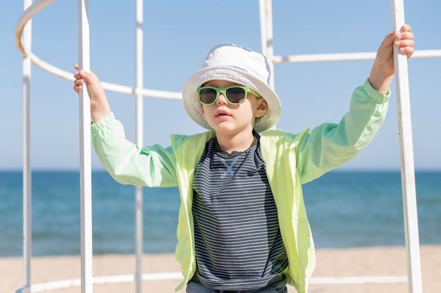 Rapaz com óculos de sol à beira-mar