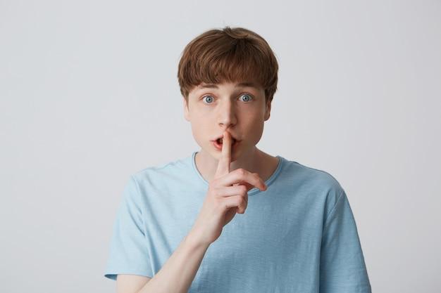 Rapaz com os olhos bem abertos, mantém o dedo da frente nos lábios