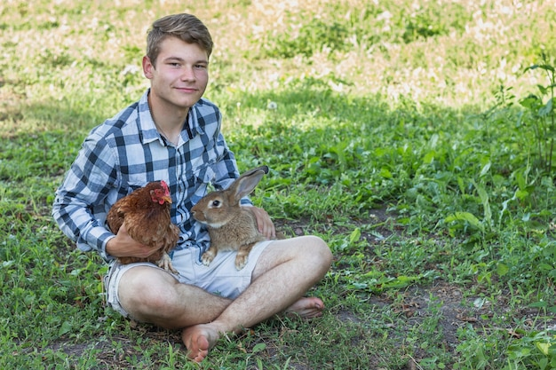 Rapaz com pernas cruzadas segurando coelhos e frango
