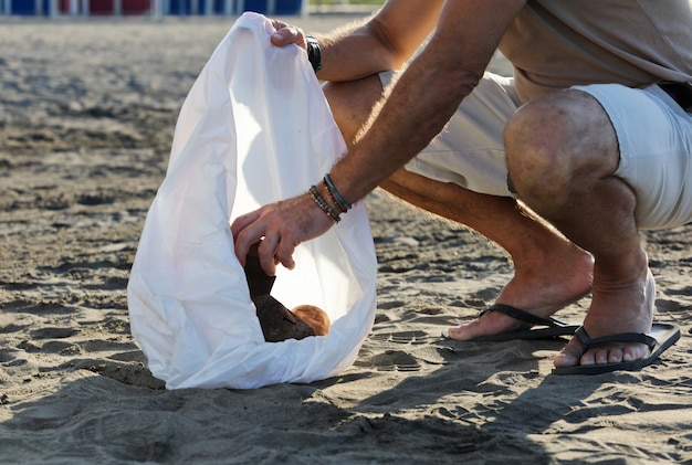 Rapaz com saco de lixo e latas enferrujadas dentro de casa na praia