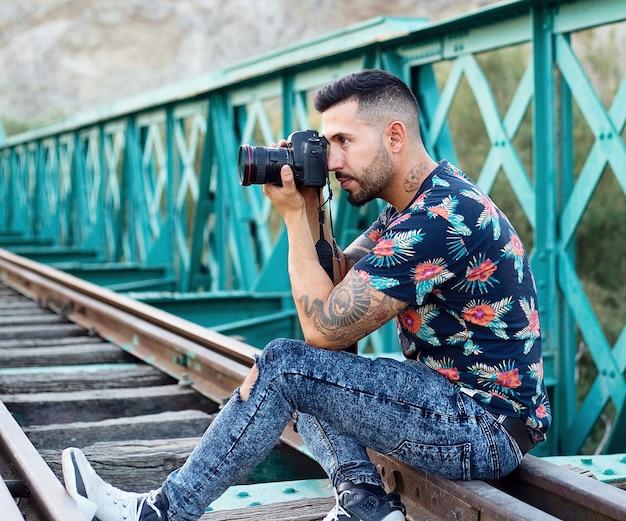 Rapaz com tatuagens e camisa de flores, tirando fotos com a câmera, sentado nos trilhos de uma ponte