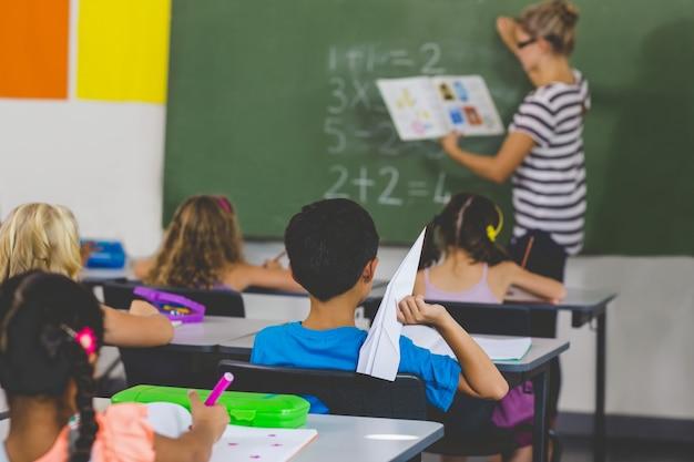 Rapaz com um avião de papel enquanto professor ensinando em sala de aula