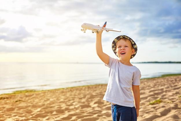 Rapaz com um avião nas mãos na praia