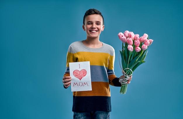 Rapaz com um suéter listrado multicolorido segura um buquê de flores de tulipa e um cartão postal para sua mãe, isolado em um azul.
