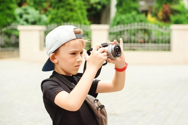 Rapaz com uma câmera digital, tirando fotos. profissão futura. férias de verão, lembranças e impressões.