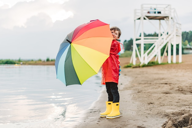 Rapaz com uma capa de chuva vermelha e botas de borracha amarelas na margem do rio segurando um guarda-chuva arco-íris
