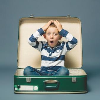 Rapaz com uma expressão de surpresa, sentado dentro de uma mala