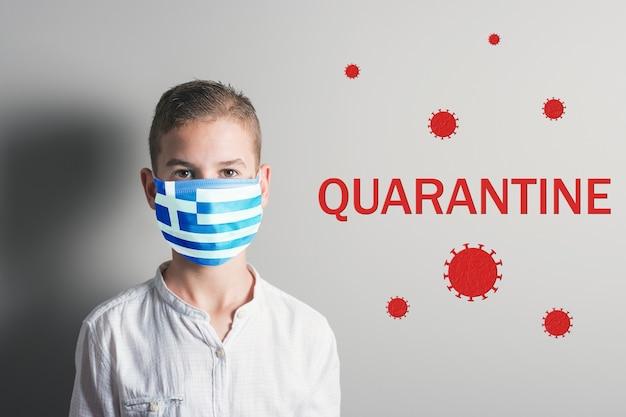 Rapaz com uma máscara médica com a bandeira da grécia no rosto no fundo brilhante.