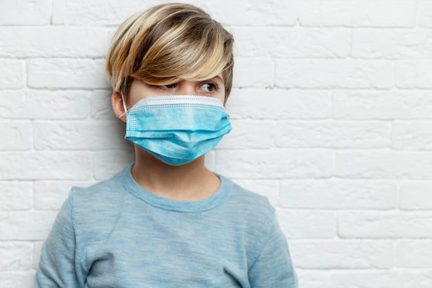 Rapaz com uma máscara médica. um menino de 9 anos com um suéter azul olha para o lado.