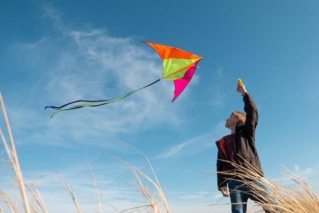 Rapaz com uma pipa. dia ensolarado de outono. o conceito de liberdade e uma infância alegre.