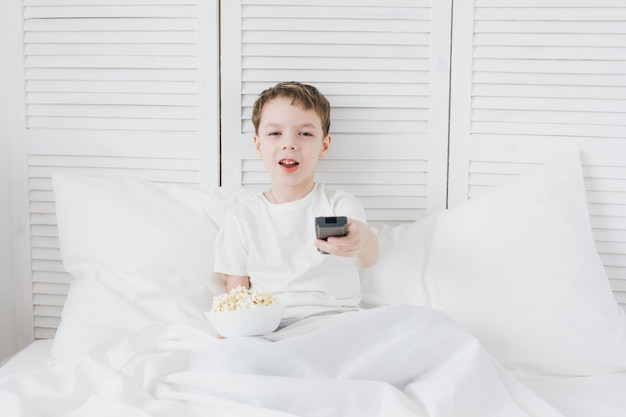 Rapaz comendo pipoca sentado na cama e assistindo tv